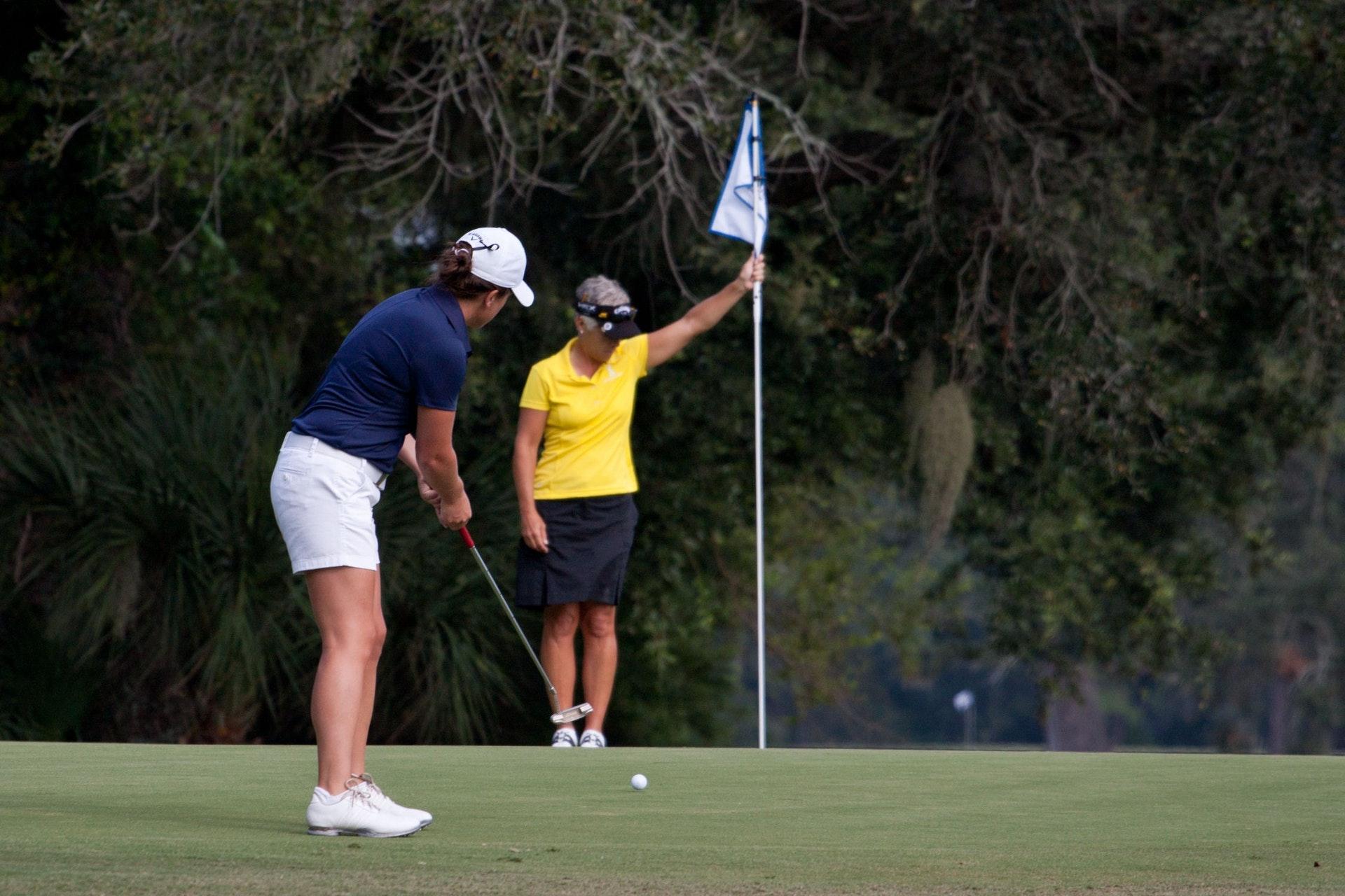 Two women playing golf